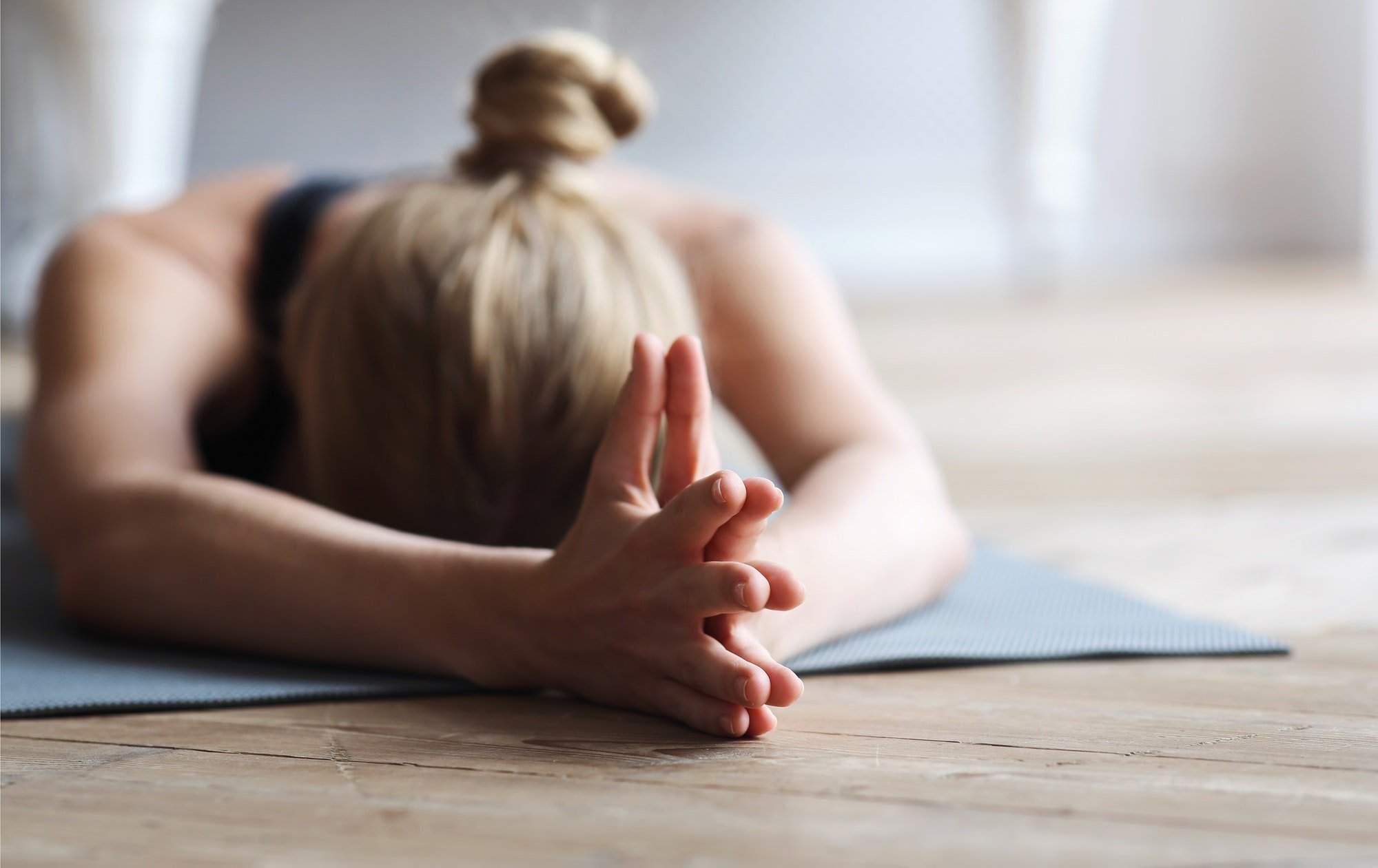 Fit girl laying face down on yoga mat, stretching